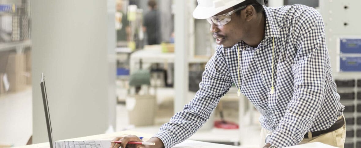 Man in hard hat and goggles examining blueprint