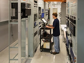 Man using a computer console to test a panel